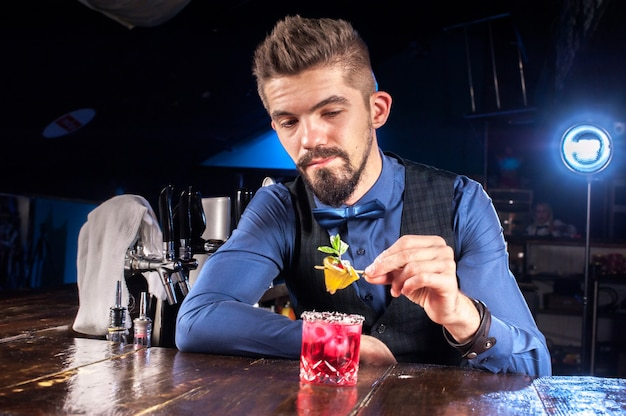 Charmante vrouwelijke barman maakt een cocktail in de pub