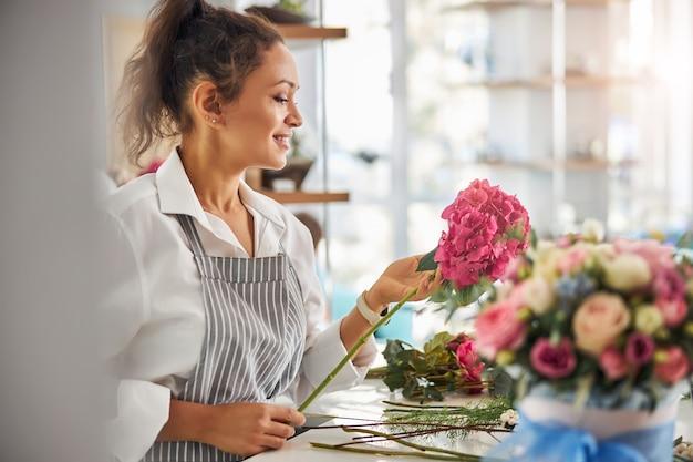 Charmante vrouwelijke bloemist die naar een mooie roze bloem kijkt