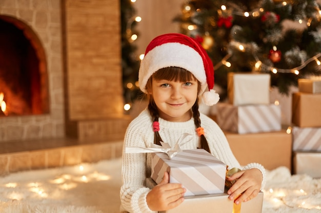 Charmante vrouwelijke jongen die een stapel cadeautjes vasthoudt, een klein kind met een witte trui en een kerstmuts, zittend op de vloer bij de kerstboom, cadeautjes en een open haard.