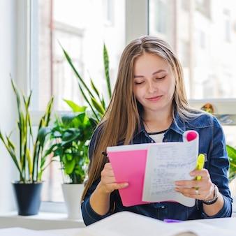 Charmante vrouwelijke studenten lezen notities