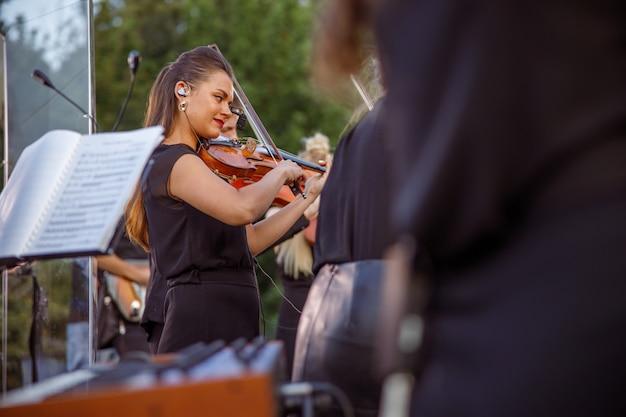 Charmante vrouwelijke violist spelen in orkest op straat