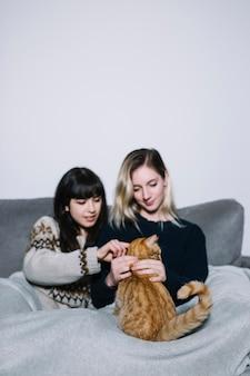 Charmante vrouwen die met kat knuffelen