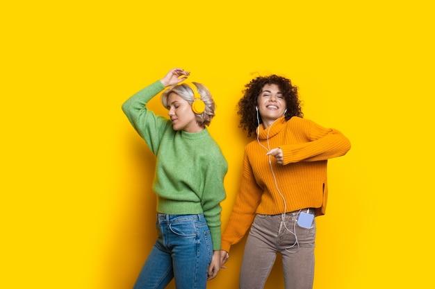 Charmante vrouwen met krullend haar dansen terwijl ze luisteren naar muziek in een koptelefoon op een gele studiomuur met warme truien en een glimlach