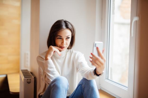 Charmante vrouwenzitting op vensterbank in jeans met telefoon die selfie maken