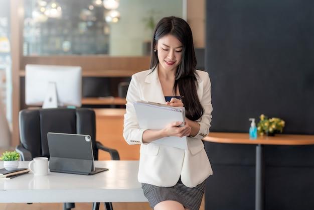 Charmante zakenvrouw die op kantoor staat en notities maakt over documenten.