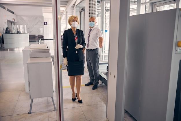 Charmante zakenvrouw met medisch masker die door de incheckpoort gaat terwijl een mannelijke luchthavenmedewerker achter haar staat