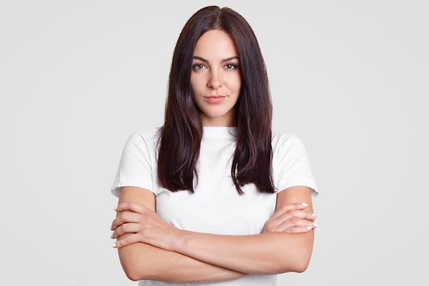 Charmante zelfverzekerde brunette vrouw met een gezonde huid, houdt armen gevouwen, gekleed in casual t-shirt, luistert aandachtig informatie, geïsoleerd op wit. mensen en ernst