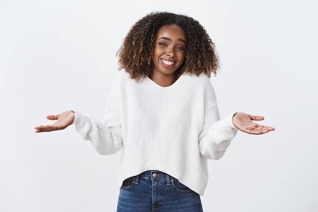 Charmante zorgeloze chill lachende afro-amerikaanse vrouw krullend kapsel schouderophalend handen zijwaarts gespreid kijken ongehinderd geen interesse geven, staande geen idee, niet op de hoogte witte muur