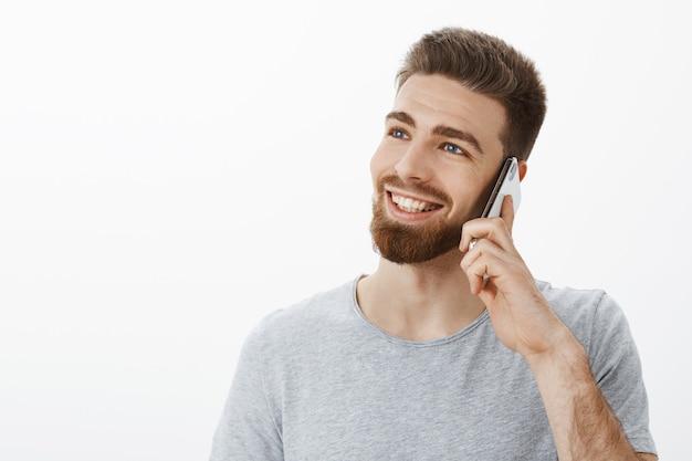 Charmante, zorgeloze jonge succesvolle ondernemer met blauwe ogen en baard die mobiel in de buurt van oor houdt en naar links kijkt met een dromerige, vrolijke blik, glimlachend terloops pratend via smarpthone over witte muur
