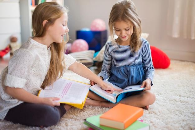 Charmante zussen die door hun avonturenboeken bladeren