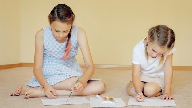 Charmante zussen zittend op de vloer met papieren en tekenen met aquarellen thuis