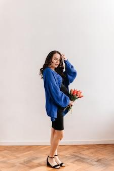 Charmante zwangere vrouw in blauw vest houdt tulpenboeket. gelukkige jonge dame in zwarte jurk vormt met bloemen op geïsoleerd.