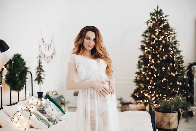 Charmante zwangere vrouw poseert voor de camera in witte jurk in de buurt van kerstboom met een lor van lichten