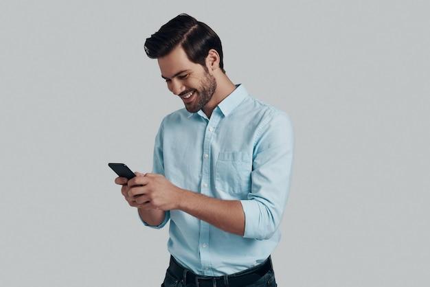 Chat met een vriend. knappe jonge man die slimme telefoon gebruikt en glimlacht terwijl hij tegen een grijze achtergrond staat