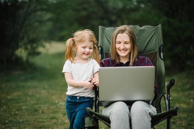Chat online met familie op laptop op picknick in de natuur. thuisonderwijs, freelance baan. moeder en kind. moeder werkt op internet met kind buitenshuis.