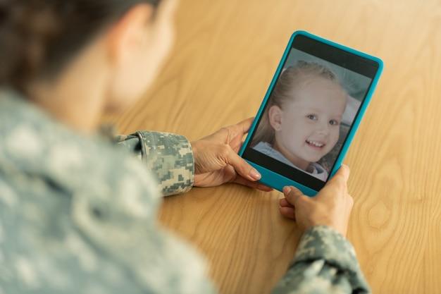 Chatten met dochter. rijpe vrouw in militair uniform chatten met dochter met behulp van tablet