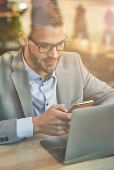 Chatten met een verticale foto van een vriend van een jonge knappe zakenman of mannelijke freelancer die zijn . gebruikt