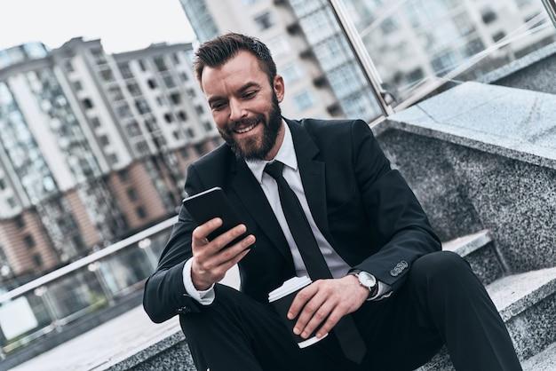 Chatten met klant. knappe jongeman in volledig pak die zijn smartphone gebruikt en glimlacht