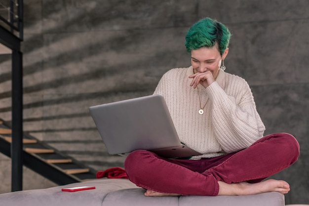 Chatten met vrienden. groenharige vrolijke vrouw die lacht terwijl ze videochat met vrienden