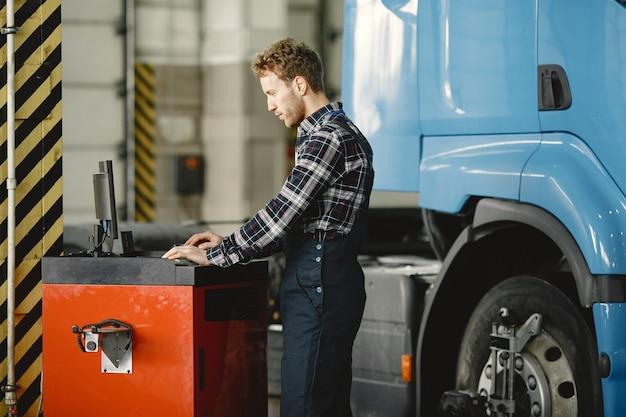 Chauffeur controleert de goederen. man in uniform. vrachtwagen in de garage