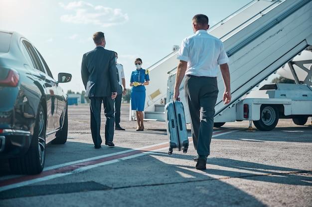 Chauffeur draagt de bagage van de baas terwijl hij met hem van auto naar vliegtuig loopt tijdens pandemie
