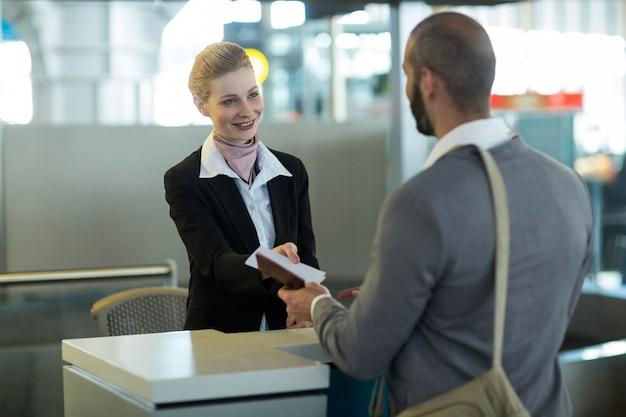 Check-in begeleider van de luchtvaartmaatschappij die paspoort aan de forens overhandigt