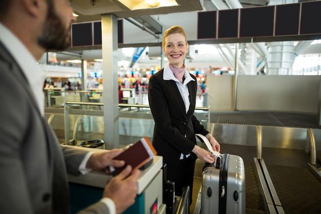 Check-in begeleider van een luchtvaartmaatschappij die een label aan de bagage van de forens plakt