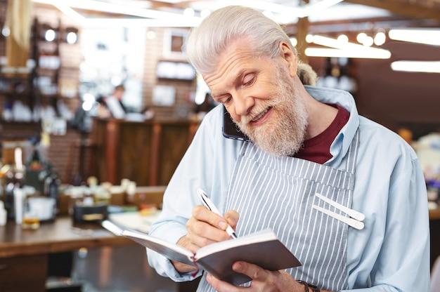 Check lijst. vrolijke mannelijke persoon buigend hoofd tijdens het maken van mededelingen in notitieblok