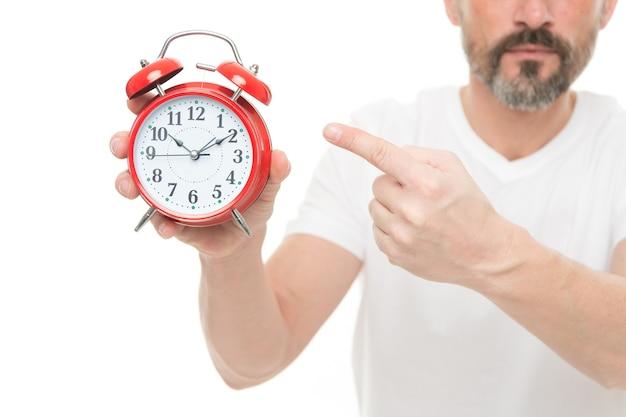 Check tijd. man houdt wekker in de hand. guy bebaarde volwassen man maakt zich zorgen over de tijd. hoe laat is het. timemanagement en discipline. punctualiteit en verantwoordelijkheid. man met klok op witte achtergrond.