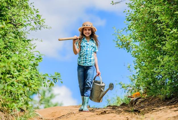Checklist voor de lentetuin. kleine helper. bewateringshulpmiddelen die droge tuinproblemen oplossen. verwijderbare roos zorgt voor een matige stroom. tuintips. lente tuinieren. meisje kind houd schop gieter.