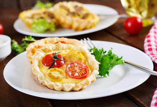 Cheddar, tomatentartlets op houten achtergrond. mini taarten. heerlijk voorgerecht, tapas, snack.