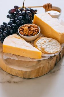 Cheddarkaas, druiven, noten, honing en cracker in houten plank op marmer