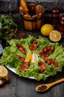 Chee kofta turkse rauwe gehaktbal plaat op sla bladeren met citroen