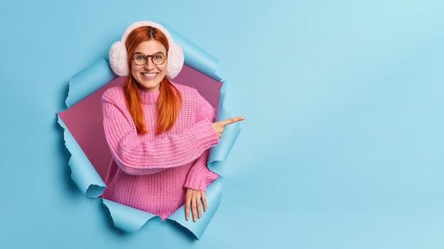 Cheeful mooie europese vrouw met natuurlijk rood haar draagt warme oorwarmers en gebreide trui wijzend op kopie ruimte, breekt door papieren gat.