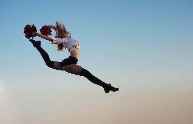 Cheerleademeisje met pompoms voert acrobatisch element in openlucht op het dak uit