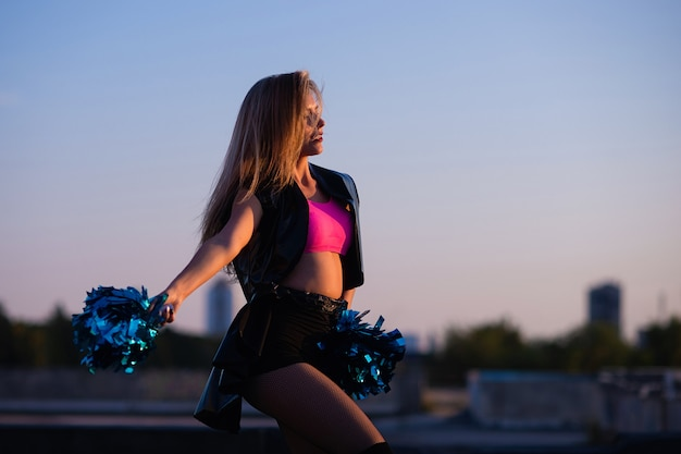 Cheerleader met pompoms die in openlucht op het dak bij zonsondergang dansen