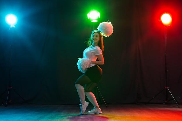 Cheerleading jonge vrouw dansen met pom-poms op kleurrijke achtergrond.