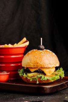 Cheeseburger in broodbroodje met frieten in rode container.