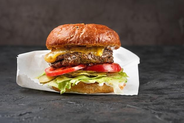 Cheeseburger met gegrild vlees, kaas, tomaat en aardappelen op een donkere stenen ondergrond. ideaal voor reclame. close-up voor menu