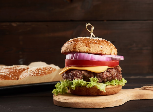 Cheeseburger met tomaten, barbecuekotelet en sesambroodje op een oude houten snijplank