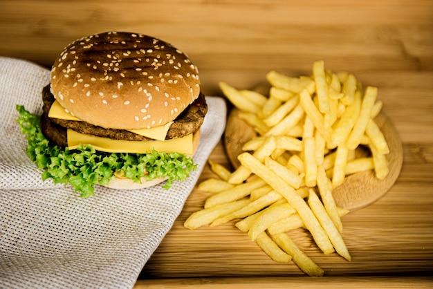 Cheeseburgers op een houten tafel naast franse frietjes, fast food