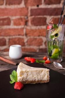 Cheesecake en aardbei op een stenen plaat op rustieke houten tafel