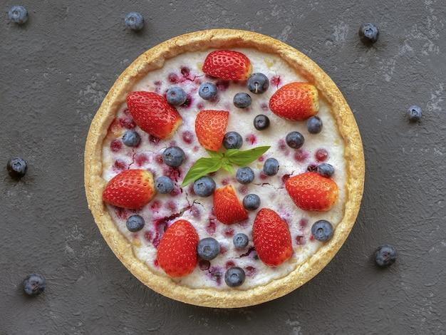 Cheesecake met aardbeien en bosbessen op betonnen tafel, bovenaanzicht