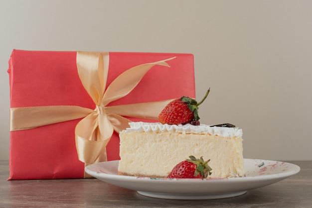 Cheesecake met aardbeien en een geschenk op marmeren tafel.