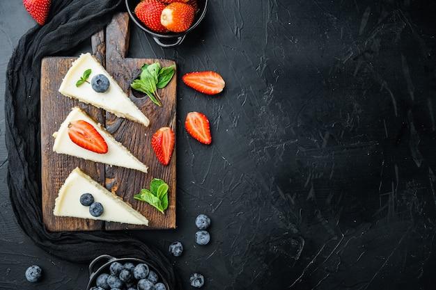 Cheesecake met bosbessen en aardbeien, op zwarte tafel, bovenaanzicht plat lag