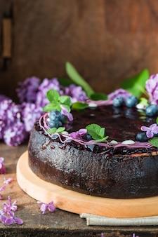 Cheesecake met bosbessensmaak gewerveld met bosbessensaus op een koekjeskruimel