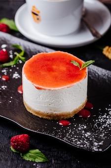 Cheesecake met frambozensiroop en muntblaadjes.