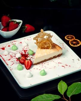 Cheesecake met gesneden aardbeien op plaat