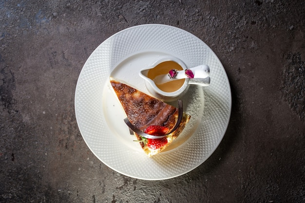 Cheesecake met kaasvulling met aardbeien op een wit bord bovenaanzicht