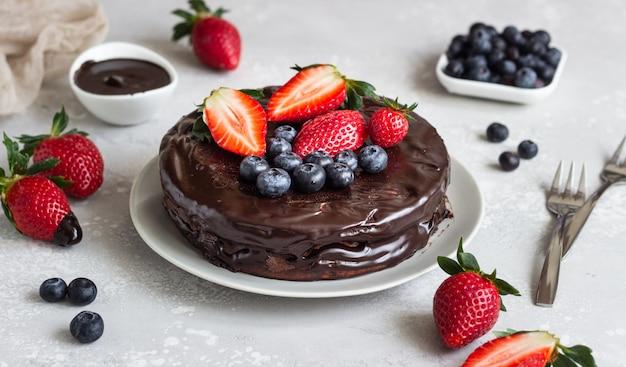Cheesecake met rozijn versierd met chocoladeglans en aardbeien en bosbessen.